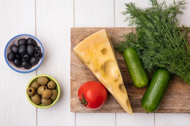 Draufsicht maasdam käse mit gurkendill und tomate auf einem stand mit oliven auf einem weißen hintergrund