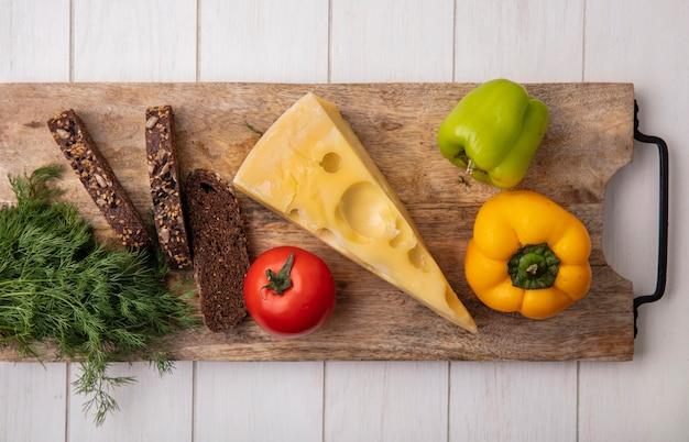Draufsicht maasdam käse mit scheiben von schwarzbrotdilltomate und paprika auf einem ständer