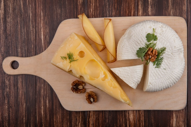 Draufsicht maasdam und feta-käse mit nüssen auf einem stand auf einem hölzernen hintergrund