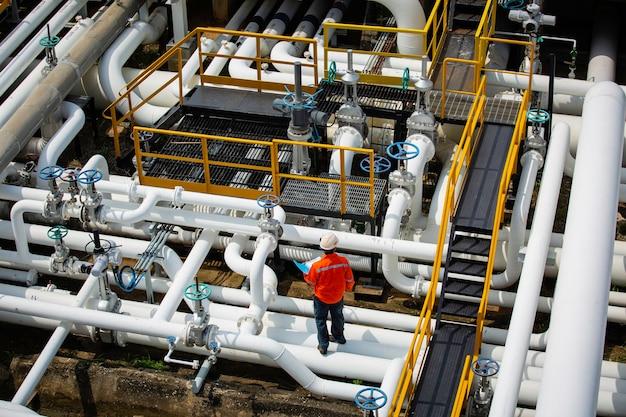 Draufsicht männlicher arbeiter inspektion am ventil der visuellen prüfprotokoll-pipeline öl- und gasindustrie Premium Fotos