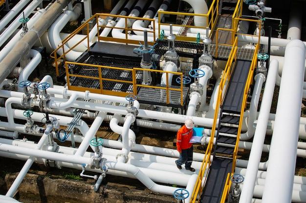 Draufsicht männlicher arbeiter inspektion am ventil der visuellen prüfprotokoll-pipeline öl- und gasindustrie