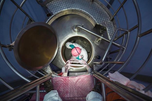 Draufsicht männlicher arbeiter klettert die treppe hinauf in den rostfreien chemikalienbereich des tanks sicherheit auf engstem raum