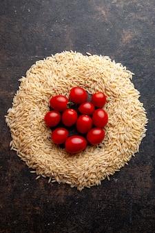 Draufsicht makkaroni in einer kreisform mit tomaten auf ihnen auf dunklem strukturiertem hintergrund. vertikale