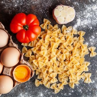 Draufsicht makkaroni mit eiern, tomate und knoblauch auf dunklem strukturiertem hintergrund.