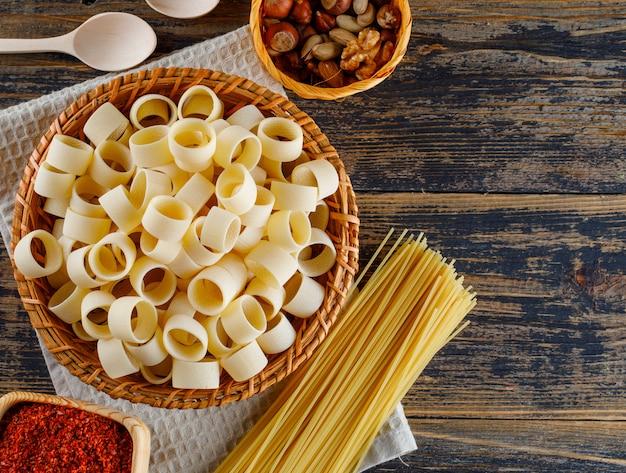 Draufsicht makkaroni-nudeln im korb mit spaghetti, löffeln, verschiedenen nüssen auf hölzernem hintergrund. horizontaler raum für text
