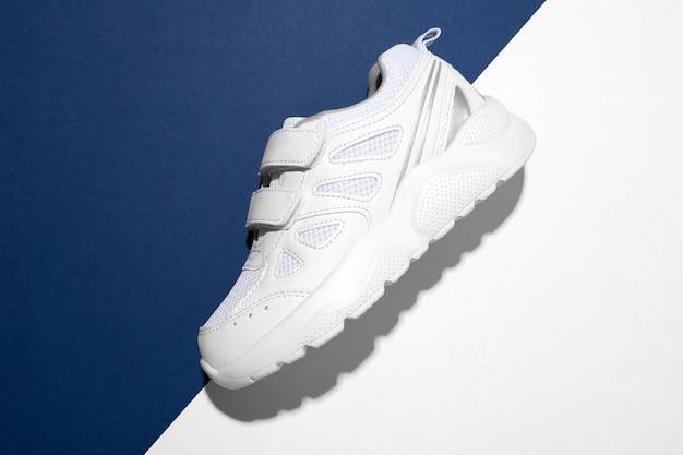 Draufsicht makro an der seite ein weißer sneaker mit klettverschluss für bequemes schuhwerk auf modernem blau...