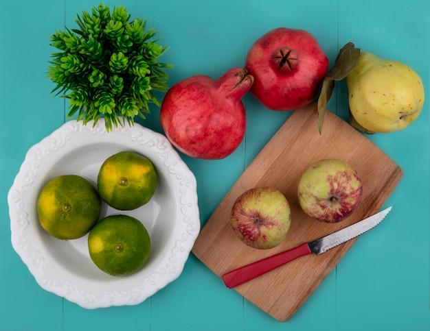 Draufsicht mandarinen in einem teller mit äpfeln auf einem schneidebrett und granatäpfeln mit birne
