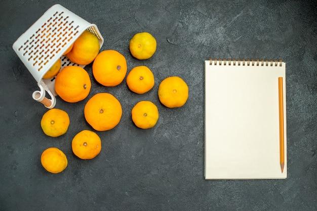 Draufsicht mandarinen und orangen verstreut aus plastikkorb notebook bleistift auf dunklem hintergrund