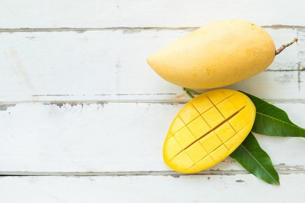 Draufsicht mangos mit geschnittenen und grünen blättern auf holztisch mit leerer linker seite.