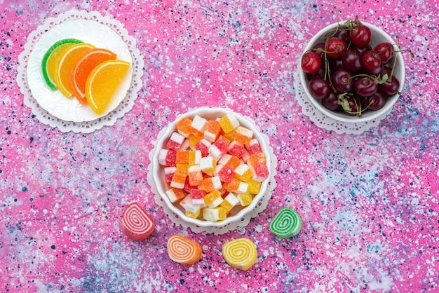 Draufsicht marmeladen und kirschen auf der bunten hintergrundfarbe snack candy goody