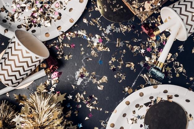 Draufsicht marmortisch mit partybecher, partygebläse, lametta, konfetti