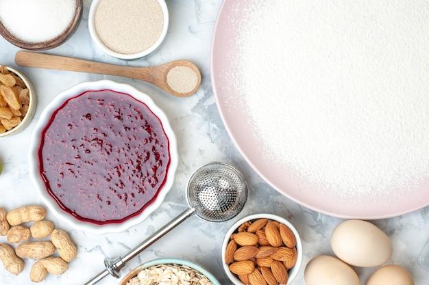Draufsicht mehl auf teller schüsseln mit mehl hafer mandeln marmelade walnuss eier holzlöffel auf tisch