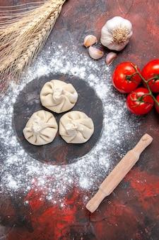 Draufsicht mehl knoblauch nudelholz khinkali mehl tomaten mit stielen
