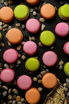 Draufsicht mehrfarbige macarons mit kieselsteinen auf schwarzem tisch