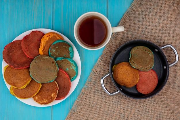 Draufsicht mehrfarbige pfannkuchen auf einem teller und in einer pfanne mit einer tasse tee auf einer beigen serviette auf einem türkisfarbenen hintergrund