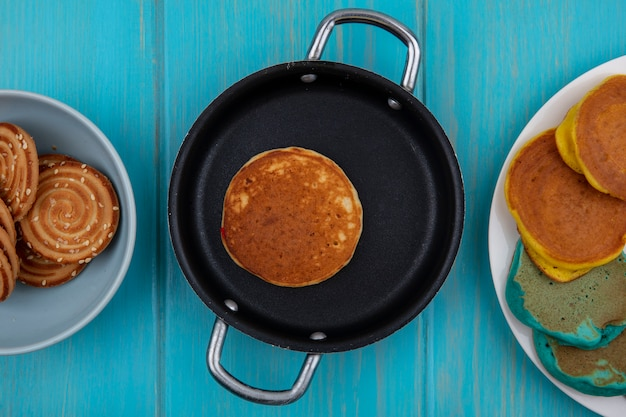 Draufsicht mehrfarbige pfannkuchen auf einem teller und in einer pfanne mit keksen auf einem türkisfarbenen hintergrund