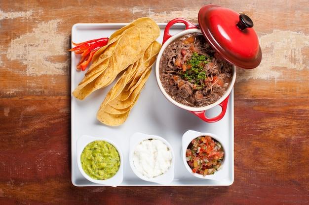 Draufsicht mexikanische tacos mit zerkleinertem fleisch guacamole, saurer sahne, tomatensauce, salsa und glühenden chilischoten auf holztisch