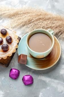 Draufsicht milchkaffee mit kirschkuchen und bonbons auf dem hellen tischkuchenkeks süßer zuckerauflauf