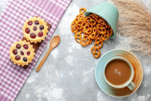 Draufsicht milchkaffee mit kleinen kuchen und crackern auf dem hellen hintergrundkuchenkeks süßer zuckerauflauf