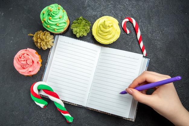 Draufsicht mini bunte cupcakes ein notizbuch weihnachtsbonbons und ornamente stift in der frauenhand auf dunklem hintergrund