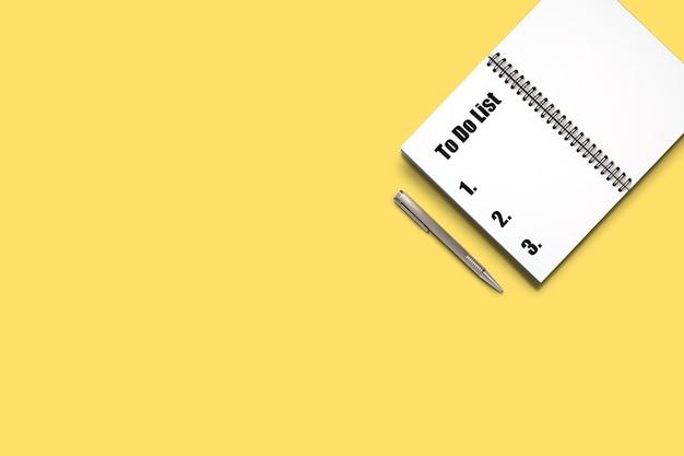 Draufsicht minimales design des geöffneten notizbuchs mit stift und listenformulierung auf gelbem hintergrund.