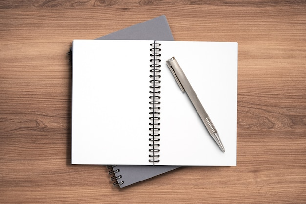 Draufsicht minimales design des offenen notizbuchmemos mit metallstift auf hölzernem hintergrund.