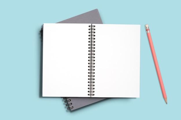 Draufsicht minimales design des offenen notizbuchmemos mit rosa bleistift auf blauem hintergrund.