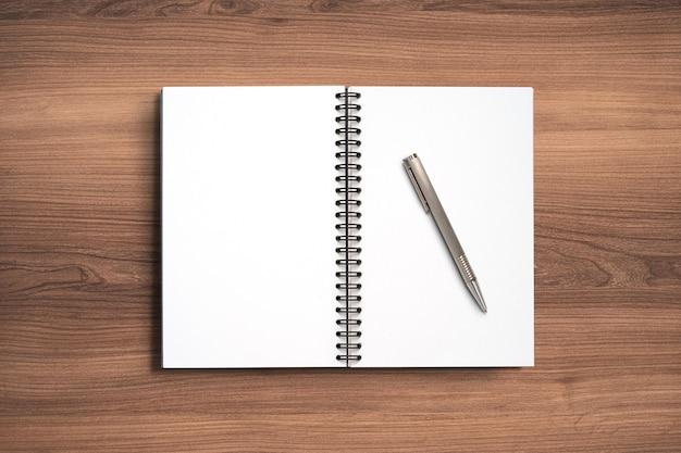 Draufsicht minimales design des offenen notizbuchs mit stift auf hölzernem hintergrund.