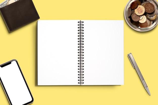 Draufsicht minimales design des offenen notizbuchs mit stiftgeldbörse und münzglas zum speichern des konzepts.