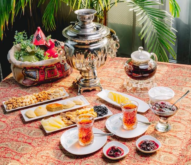 Draufsicht mischen teeservice für zwei personen mit einer samowar-teekanne und süßigkeiten auf dem tisch