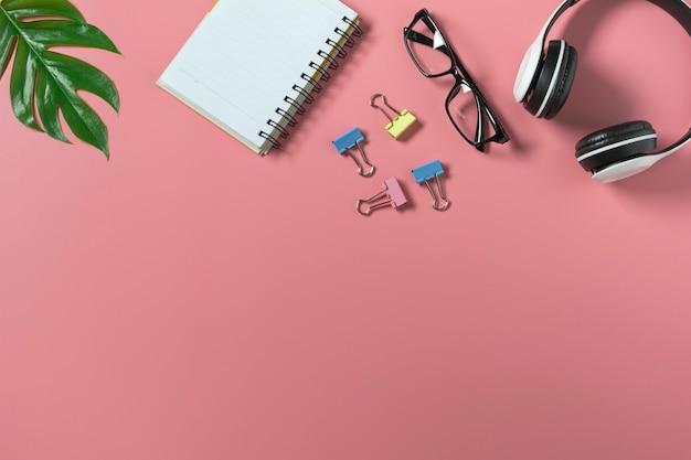 Draufsicht mit der brille, dem notizbuch und dem kopfhörer auf rosa hintergrundgruppe. überfüllter schreibtisch.