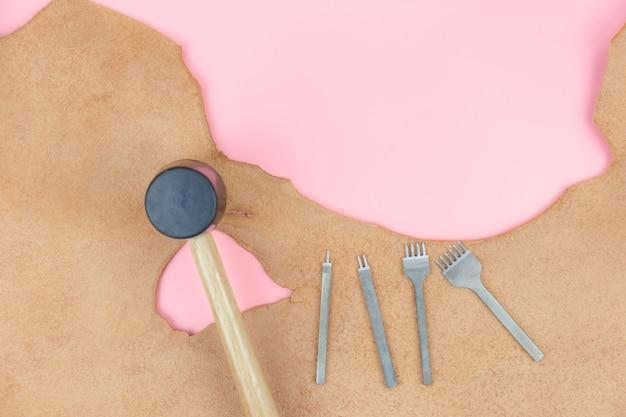 Draufsicht mit der lederhandwerkswerkzeuggruppe, diamantlocherhammer obenliegend auf rosa pastellhintergrund, lederhandwerk oder lederner arbeitsebenenlage