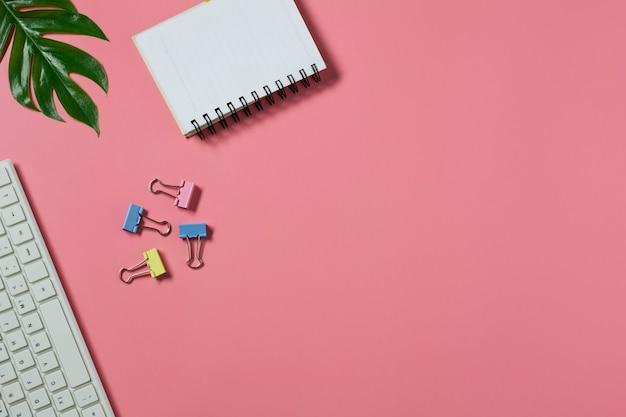 Draufsicht mit der tastatur und dem notizbuch auf rosa raum. überfüllter schreibtisch