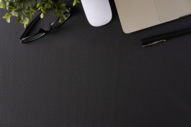Draufsicht mit kopienraum der ledernen schreibtischtabelle des büros mit computerzubehör.