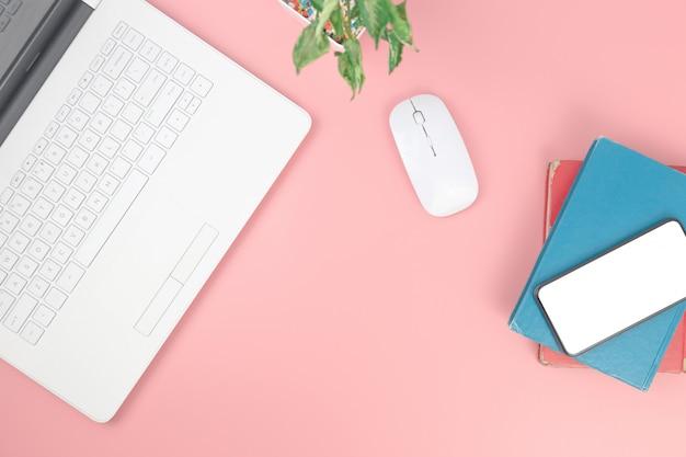 Draufsicht mit laptopnotizbuch smartphone auf den büchern obenliegend auf rosa pastellhintergrund, ebenenlage