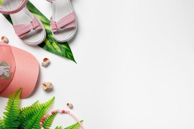 Draufsicht mit sommeraccessoires mädchenaccessoires rosa sandalen und mütze mit grünen tropischen blättern...