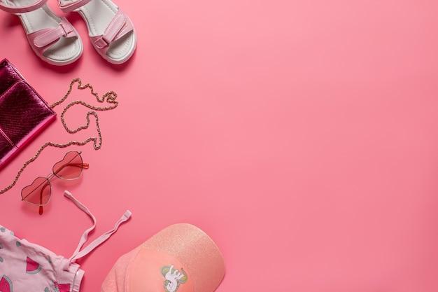 Draufsicht mit sommerkleidung. mädchenkleidung und accessoires, tasche, sandalen, baseballmütze auf rosa hintergrund. ansicht von oben.