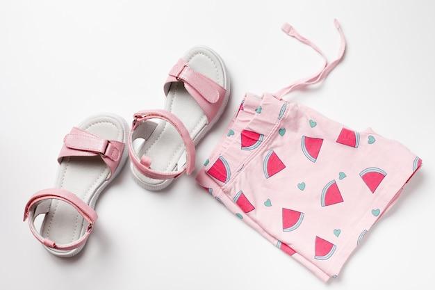 Draufsicht mit sommerschuhen und kleidung mädchen rosa shorts und sandalen auf dem weißen isolierten hintergrund