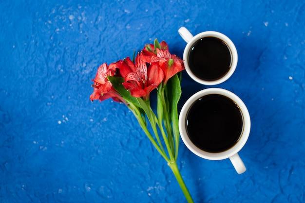 Draufsicht mit zwei tassen kaffee mit roter blume auf dem kopienraum.