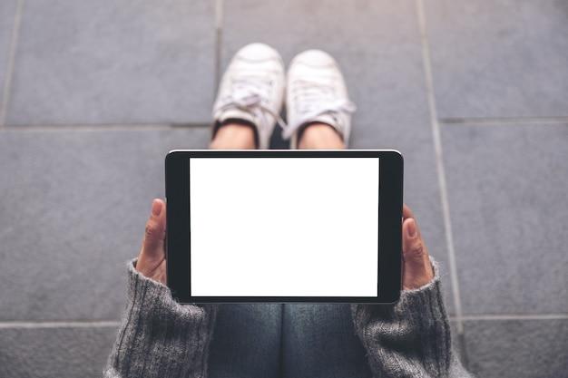 Draufsicht-modellbild der hände der frau, die schwarzen tablet-pc mit leerem weißen desktop-bildschirm halten und verwenden, während auf dem boden sitzend