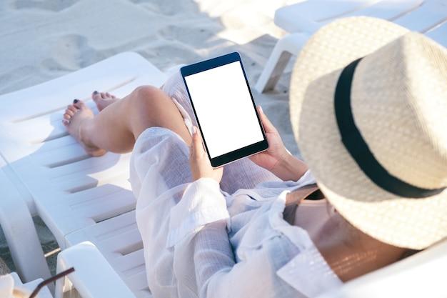 Draufsicht-modellbild einer frau, die einen schwarzen tablett-pc mit leerem desktop-bildschirm hält, während auf strandkorb am strand liegend