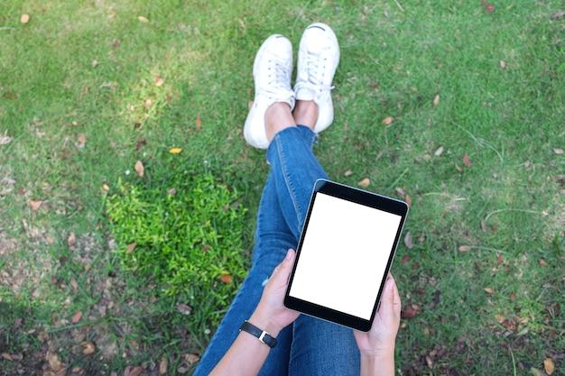 Draufsicht-modellbild einer frau, die schwarzen tablett-pc mit leerem weißen desktop-bildschirm hält und verwendet, während im freien sitzen