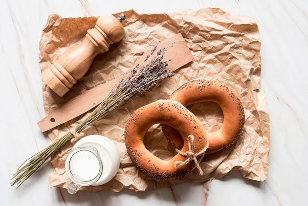 Draufsicht mohn bagels auf pergamentpapier mit milch