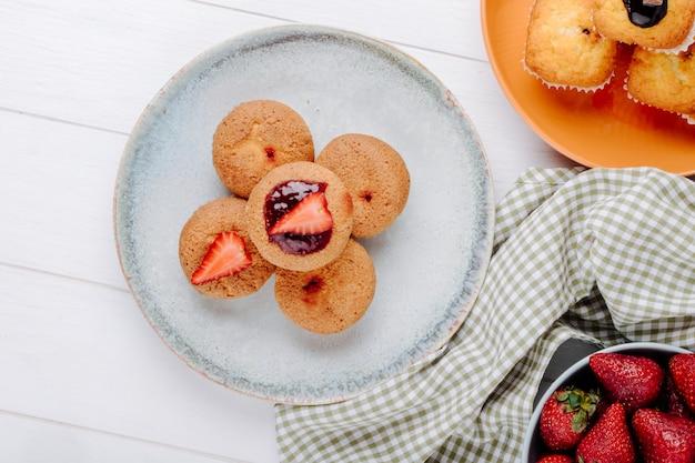 Draufsicht muffins mit erdbeeren auf einem teller mit erdbeeren auf einem teller
