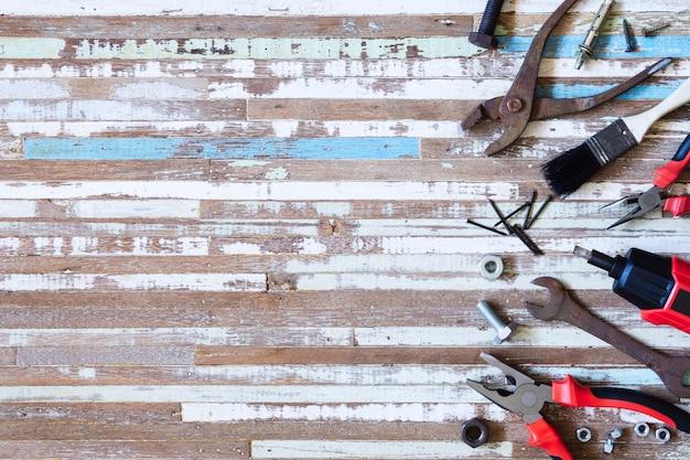 Draufsicht nah oben von den handlichen werkzeugen der vielzahl und von den rostigen werkzeugen auf hölzernem hintergrund des schmutzes mit kopienraum für ihren text