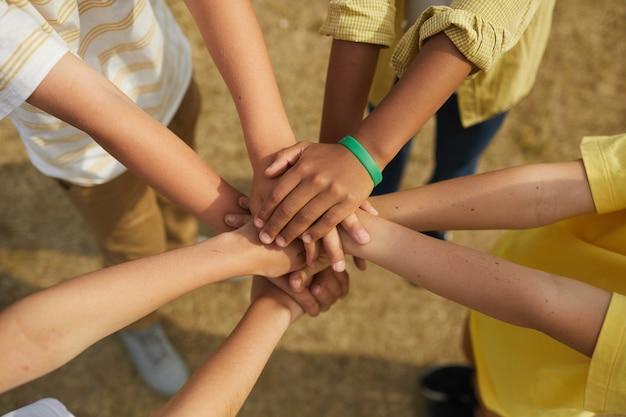 Draufsicht nahaufnahme bei multiethnischer gruppe von kindern, die hände stapeln, während sie im kreis draußen stehen, konzept der freundschaft und der einheit