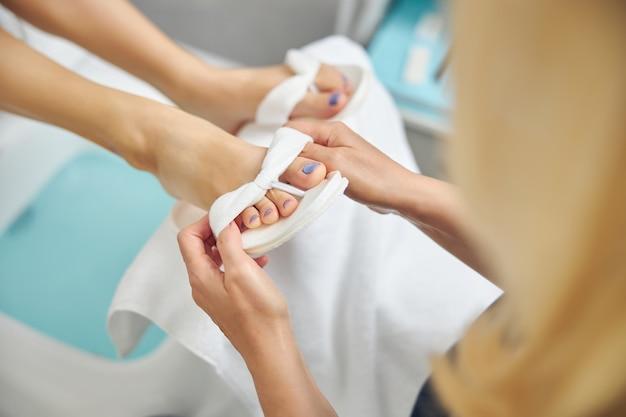 Draufsicht, nahaufnahme der dame, die sich nach der pediküre im spa-salon um weibliche füße kümmert?
