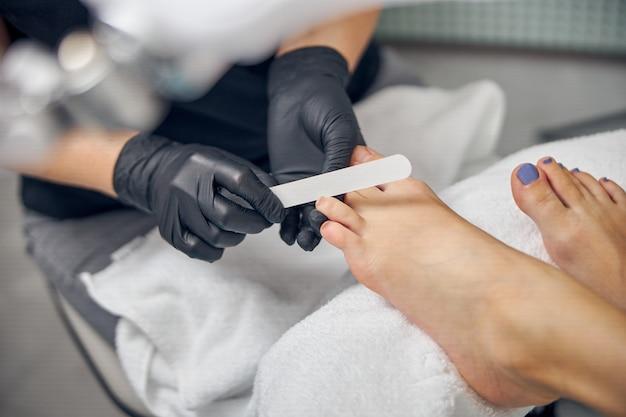 Draufsicht, nahaufnahme der füße des kunden, während der künstler eine pediküre für eine frau mit einer sterilen datei macht