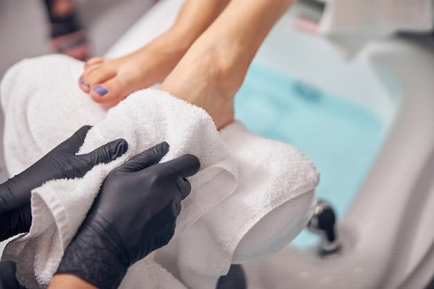 Draufsicht, nahaufnahme des nagelkünstlers in sterilen handschuhen, die weibliche füße mit handtuch trocknen