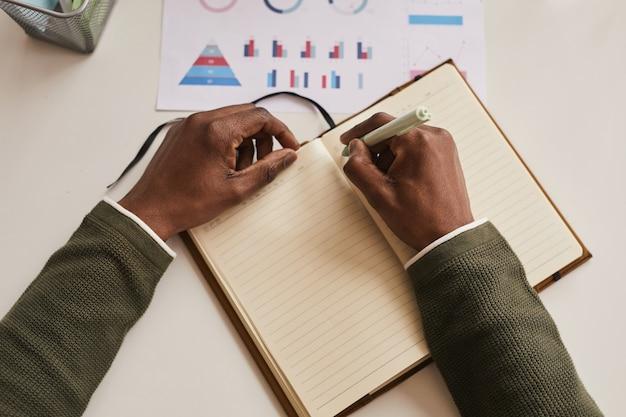 Draufsicht nahaufnahme des nicht erkennbaren mannes, der im planer schreibt, während er am schreibtisch im büro arbeitet, fokus auf männliche hände hält stift, kopienraum